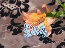 Lirio tigrado anaranjado con la muestra azul del feliz cumpleaños fotos de archivo