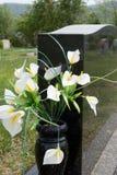 Lirios en florero de la lápida mortuaria Fotografía de archivo