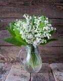 Lirios hermosos en un florero de cristal en la tabla vieja Fotografía de archivo libre de regalías