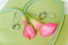 Lirios rosados con los anillos de bodas Foto de archivo libre de regalías