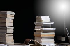 Lisant beaucoup de manuels sur la table avec des beaucoup empilement élevé photographie stock libre de droits