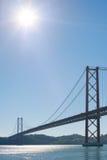 Lisboa cielo azul y sol del againt de puente colgante del 25 de abril Foto de archivo libre de regalías