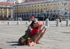 LISBOA - 10 DE JULIO DE 2014: Los turistas que toman las fotos en Praca hacen al asistente Imagenes de archivo