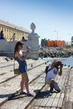 LISBOA - 10 DE JULIO DE 2014: Los turistas que toman las fotos en Praca hacen al asistente Fotos de archivo libres de regalías