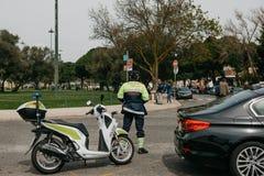 Lisboa, el 18 de junio de 2018: El policía de la patrulla al lado de la motocicleta guarda el orden público Un representante de l imagenes de archivo