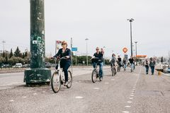 Lisboa, o 18 de junho de 2018: Um grupo de povos positivos ou os turistas montam bicicletas ao longo de uma rua da cidade na área Fotos de Stock