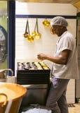 LISBOA, PORTUGAL - 17 DE ABRIL DE 2019: O cozinheiro chefe prepara pastelarias portuguesas tradicionais Cor pastel de Nata em Lis imagem de stock royalty free