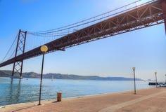 Lisboa, suspensión 25 de la señal del puente de abril Fotos de archivo libres de regalías