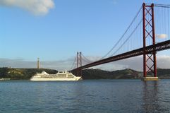 Lisbon. Cruise ship under Ponte 25 de Abril bridge in Lisbon with a view of Cristo Rei Stock Photography