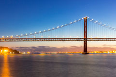 Lisbon Bridge at dusk. Lisbon cityscape with 25 de Abril suspension Bridge, Portugal at dusk Stock Photos