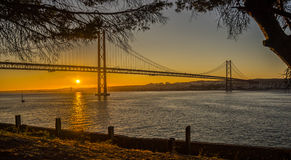 Lisbon Bridge Over tagus river sunset seen from Almada. Lisbon South Bay. Boat sailing in a river Stock Image