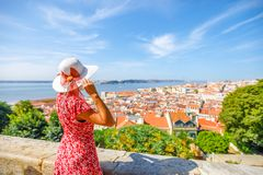 Lisbon Castle woman. Woman admires Lisbon skyline from Sao Jorge Castle in Alfama. 25 April Bridge, Tagus River and Baixa District on blurred background.Tourism Royalty Free Stock Photography
