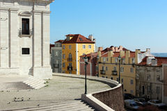 Lisbon church square surrounded by pastel houses Stock Photo