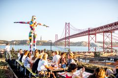 Lisbon city in Portugal. LISBON, PORTUGAL - September 27, 2017: View on the 25th of April bridge with people sitting on the bar terrace during the sunset in royalty free stock image