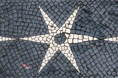 Lisbon cobblestone pavement in black white star designs royalty free stock photo