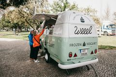 Lisbon, June 18, 2018: People buy frozen yogurt or ice cream from a street vendor. Street food and mobile commerce royalty free stock photo