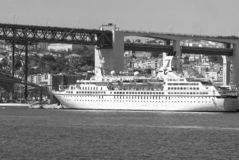 Lisbon, Portugal - April 03, 2010: ocean liner in sea port. Ship on water under bridge on sunny day. Water vessel on. Blue sea. Travelling by water. Wanderlust royalty free stock photography