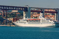 Lisbon, Portugal - April 03, 2010: ocean liner in sea port. Ship on water under bridge on sunny day. Water vessel on. Blue sea. Travelling by water. Wanderlust stock photos