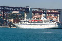 Lisbon, Portugal - April 03, 2010: ocean liner in sea port. Ship on water under bridge on sunny day. Water vessel on. Blue sea. Travelling by water. Wanderlust stock images