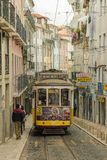Typical yellow tram number 28 riding through narrow Caveleiros s. LISBON, PORTUGAL - APRIL 20, 2018: Typical yellow tram number 28 riding through narrow stock images