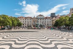 Rossio Square with famous wave pattern stone pavement. Lisbon, Portugal - August 24, 2017 Cityscape of colorful old buildings in Rossio Square, Baixa District Royalty Free Stock Images