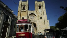 Red tram tour. Lisbon, Portugal - August 25, 2017: historic red Hills tramcar tour, famous tourist line, in front of Lisbon Cathedral in Alfama district. Lisbon stock video