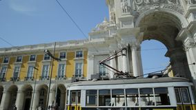 Tram 28 in Commerce Square. Lisbon, Portugal - August 25, 2017: historic yellow Tram 25 in front of Rua Augusta Triumphal Arch in Commerce Square or Praca do stock video footage