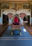 Gestatorial chair in the Lisbon Cathedral. Lisbon, Portugal, August 7, 2017: Richly adorned, silk-covered gestatorial chair with two large fans flabella made of Stock Photos