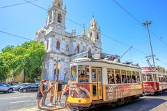 Estrela Basilica and Tram 28. Lisbon, Portugal - August 27, 2017:tourists at terminus of historic Tram 28 in front of baroque and neoclassical Estrela Basilica royalty free stock photo