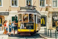 Tourists Travel By Historic Tram In Square of Luis de Camoes Of Downtown Lisbon City. LISBON, PORTUGAL - AUGUST 11, 2017: Tourists Travel By Historic Tram In royalty free stock photo