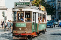 Tourists Travel By Tram 28 In Downtown Lisbon City. LISBON, PORTUGAL - AUGUST 09, 2017: Tourists Travel By Tram 28 In Downtown Lisbon City Stock Photos