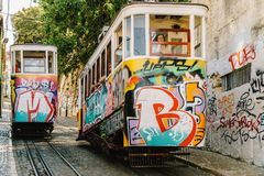 Tourists Travel By Vintage Funicular On Narrow Old Streets Of Lisbon City Stock Photos