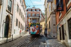 Tourists Travel By Vintage Funicular On Narrow Old Streets Of Lisbon City Stock Image