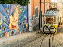 Tourists Travel By Vintage Funicular On Narrow Old Streets Of Lisbon City Stock Photo