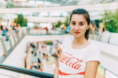 Young Girl Wearing White Shirt With Drink Coca-Cola Slogan Sign In Modern Shopping Mall Royalty Free Stock Image