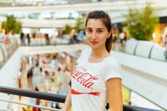 Young Girl Wearing White Shirt With Drink Coca-Cola Slogan Sign In Modern Shopping Mall Stock Images