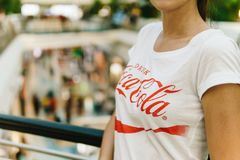 Young Girl Wearing White Shirt With Drink Coca-Cola Slogan. LISBON, PORTUGAL - AUGUST 10, 2017: Young Girl Wearing White Shirt With Drink Coca-Cola Slogan Sign Stock Image