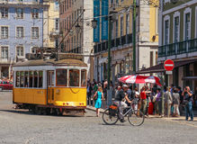 LISBON, PORTUGAL - CIRCA MAY 2014 - Old portuguese traditional electric yellow tram makes its way across central Lisbon streets Stock Photo