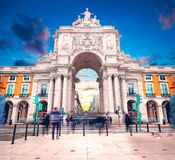 Triumphal Arch in Commerce Square at sunset with sun and clouds stock image