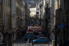 A tram electrico in a street of the Baixa neighbourhood, in the city of Lisbon. Lisbon, Portugal - February 17, 2018: A tram electrico in a street of the Baixa royalty free stock images