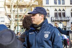 Policeman in uniform in a crowd of carnival procession. Royalty Free Stock Photos