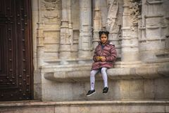 Beautiful Asian girl in fashionable clothes sitting on a bench near the monastery of Jeronimos. Lisbon, Portugal - January 2018: Beautiful Asian girl in Stock Photos