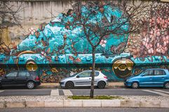 Lisbon, Portugal - January 2018: Urban subculture. City cars parked near a wall with beautiful graffiti.  Royalty Free Stock Photos