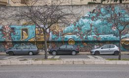 Lisbon, Portugal - January 2018: Urban subculture. City cars parked near a wall with beautiful graffiti.  Stock Images