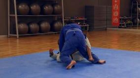 Two men practice Brazilian Jiu-Jitsu sparring, a grappling type martial arts with a kimono gi stock video footage