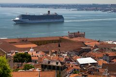 Lisbon Portugal. May 7, 2018. A huge cruise ship approaches the port of the city of Lisbon. Typical roofs of red tiles in the stock photos