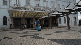 Passengers with luggage outside of Lisbon`s Santa Apolonia train station and from here the whole of Portuguese inter. Lisbon, Portugal - May 31st, 2018 stock footage