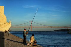 Fishing in the Tagus river at sunset in Lisbon royalty free stock images
