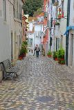 LISBON, PORTUGAL - NOVEMBER 2, 2017: narrow and colorful street in Alfama neighborhood with cobbled pavement Royalty Free Stock Image