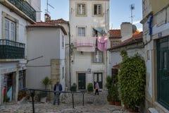 Street scene in a narrow street of the historic neighborhood of Alfama in Lisbon, Portugal Royalty Free Stock Image
